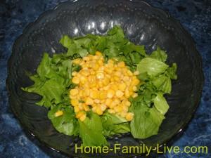 Салатные листья нарвать на куски , добавить кукурузу
